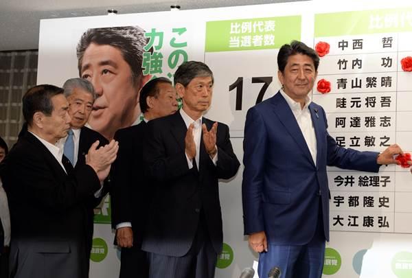 아베 신조 일본 총리(오른쪽)가 7월 10일(현지시간) 도쿄 자민당 당사에서 참의원 선거 당선자 이름 옆에 꽃을 붙이고 있다.